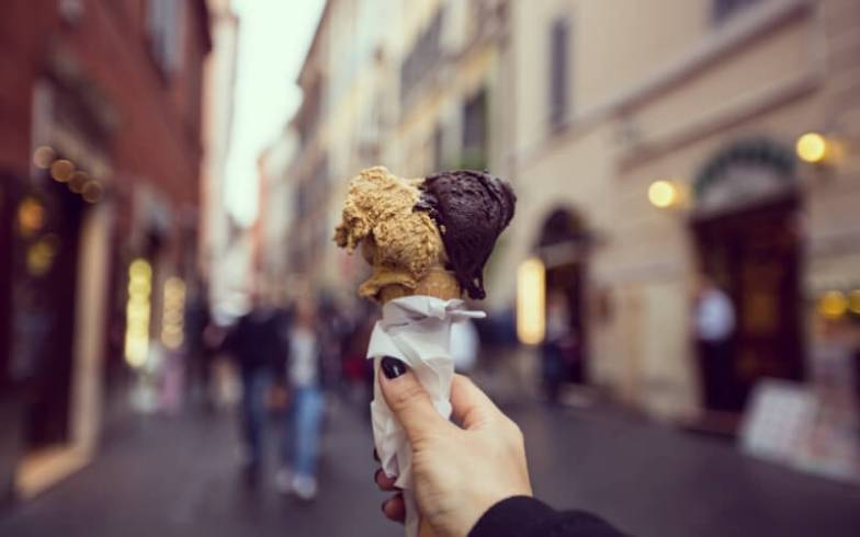 A woman holds an icecream up on the streets of Florence, Italy.