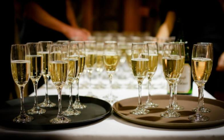 A table crowded with champagne flutes.