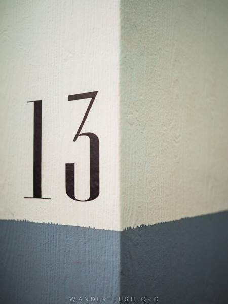 A white wall with the number 13 painted on it.