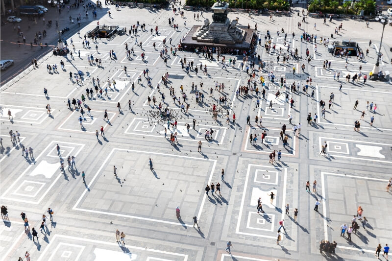 People cross a busy city plaza.