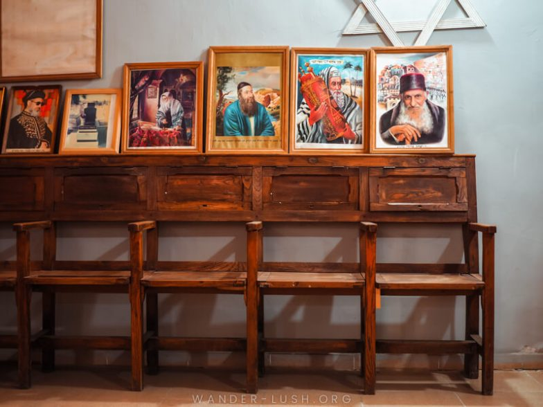 A set of wooden benches and framed Jewish religious artworks.