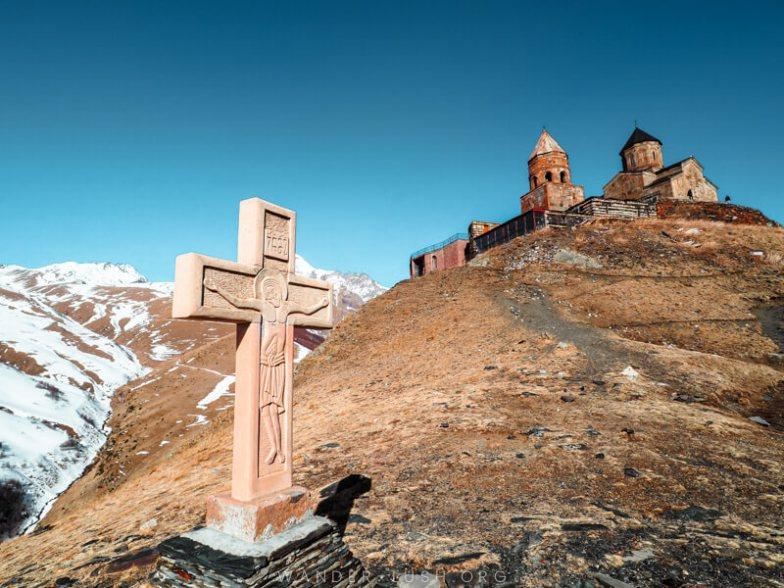A stone church and a cross atop a snowy mountain in Georgia.
