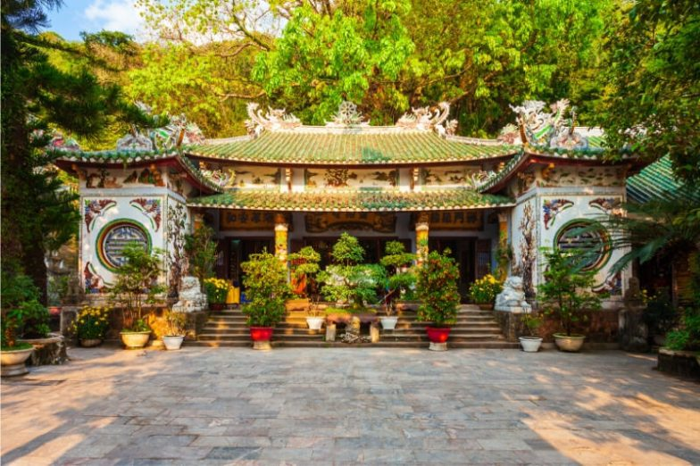 An Asian temple with potted plants out the front.