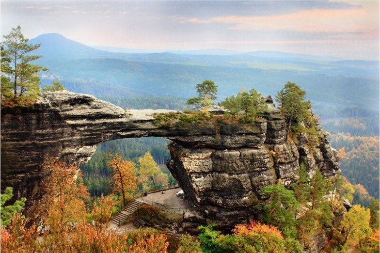 A natural stone arch surrounded by autumn foliage.