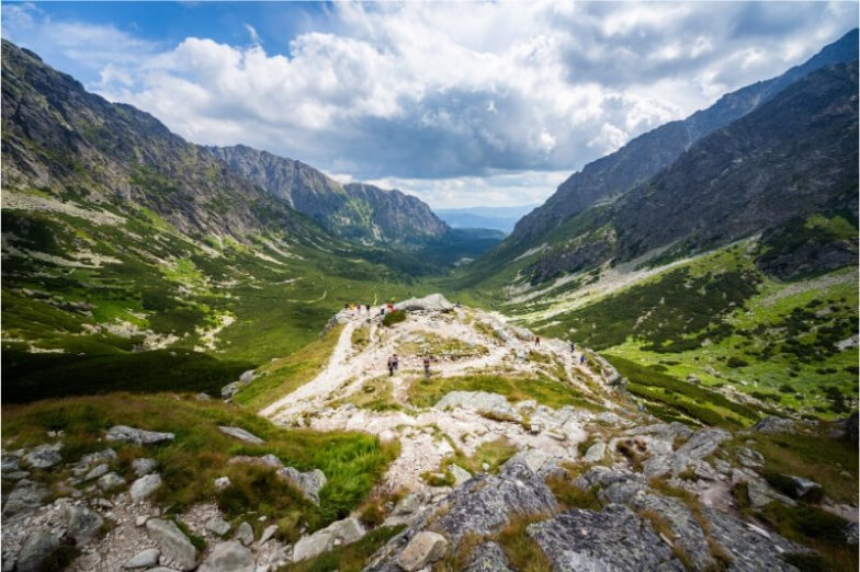 People gather on a rocky outcrop after completing a short hike in Europe in the mountains in Slovakia.