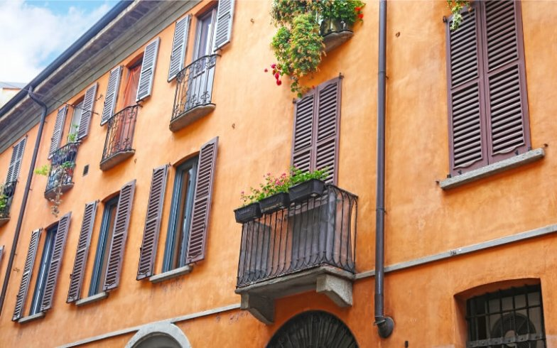 An orange house with wooden shutters and flower boxes in the colourful neighbourhoods of Milan.
