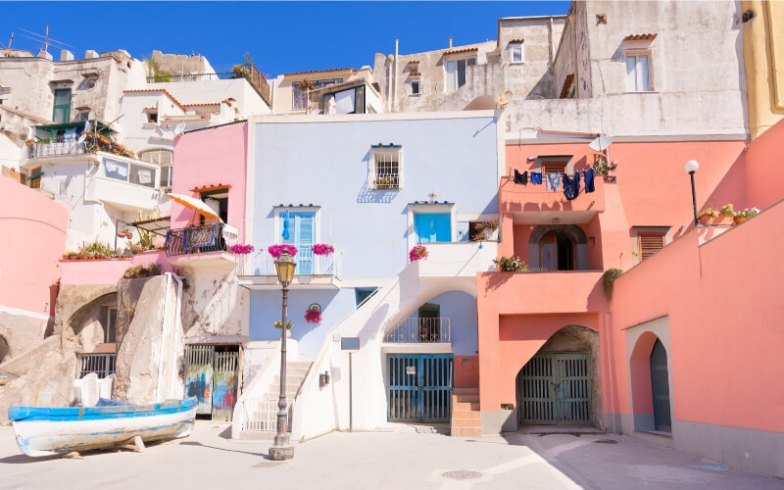 Pastel buildings creep up a hill in Procida, Italy.