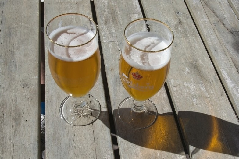 Two glasses of beer on a wooden outdoor table.