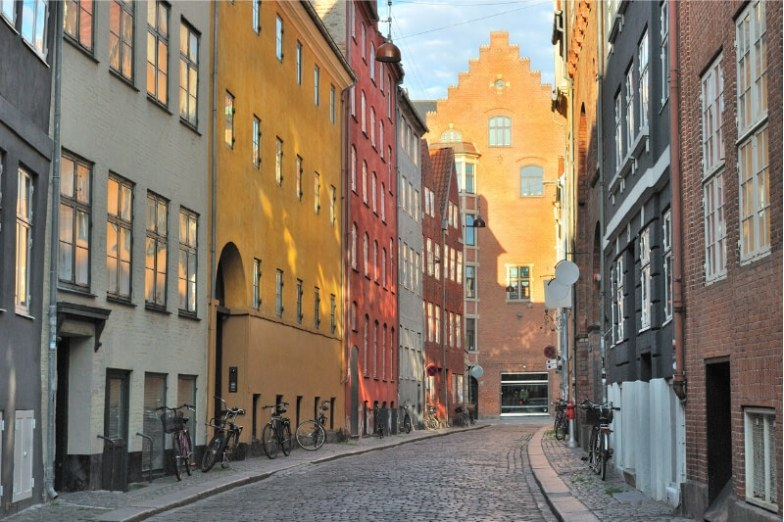 Rows of colourful buildings and bikes on a street in Copenhagen, Denmark.