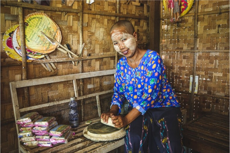 A woman prepares thanaka paste by grinding tree bark.
