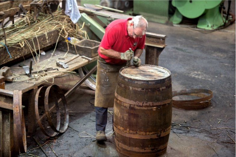 A man uses tools to make a whiskey barrel in Speyside, Scotland.