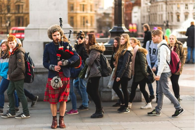 A man plays the bagpipes on a busy street in Scotland.