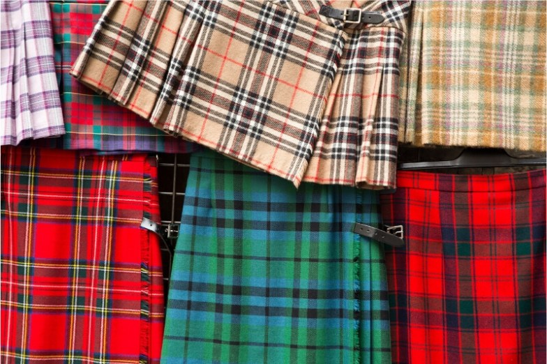 A flatlay of colourful Scottish kilts.