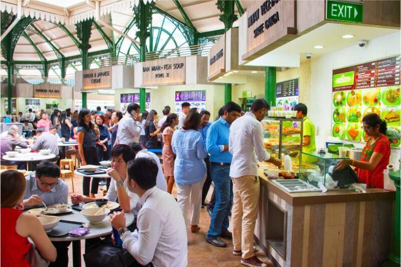 People eat inside a hawker market in Singapore.