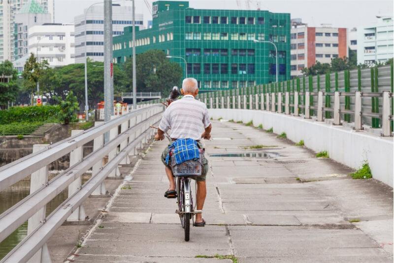 A man rides a push bike along a concrete bridge in Singapore.