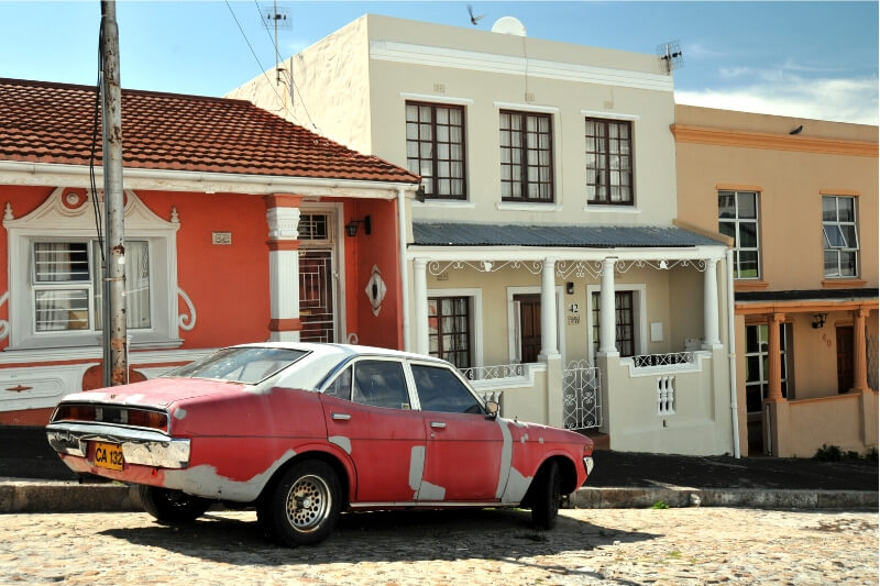 A red car parked in front of a row of colourful houses in Cape Town.