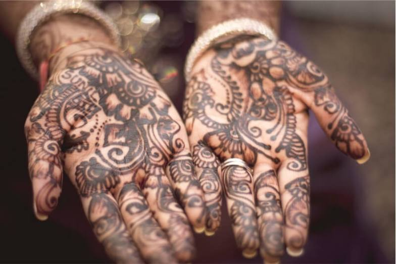 A woman's hands decorated with henna motifs.