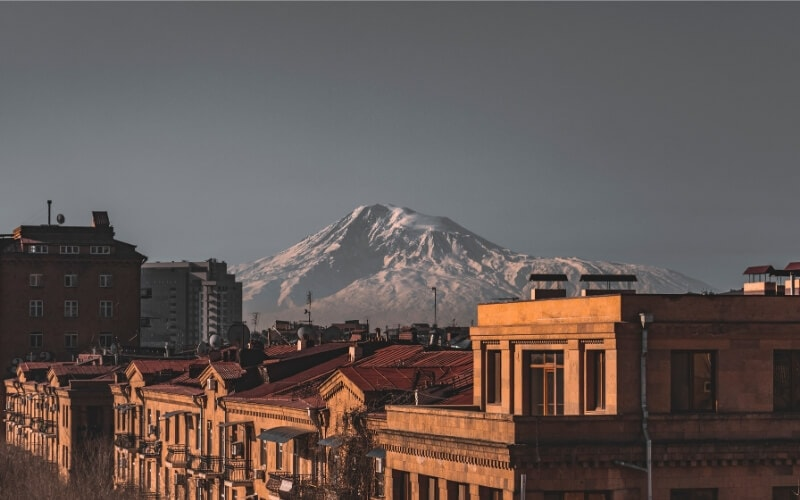 A beautiful city at dusk, with a mountain in the backdrop.