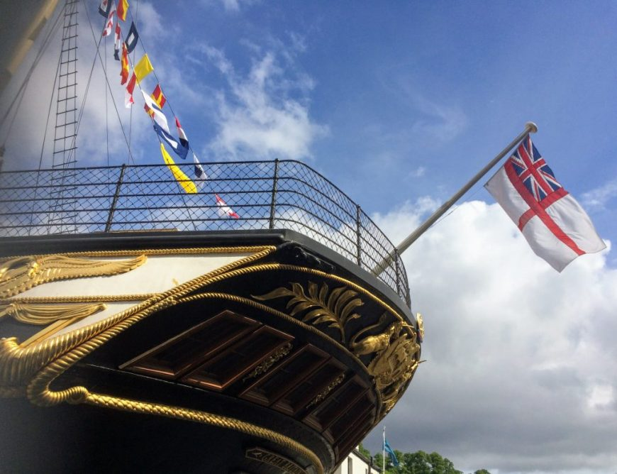 A close-up photo of the SS Great Britain ship, complete with multicultural flags flying