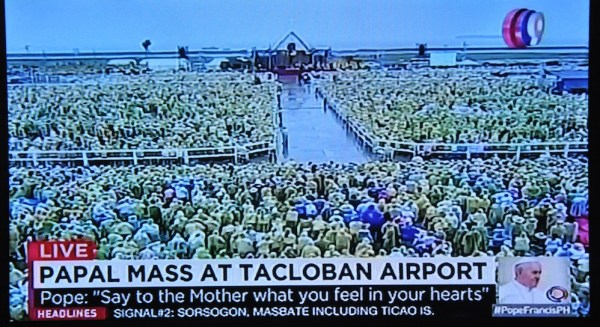 Sea of yellow raincoats intently listening to Pope Francis