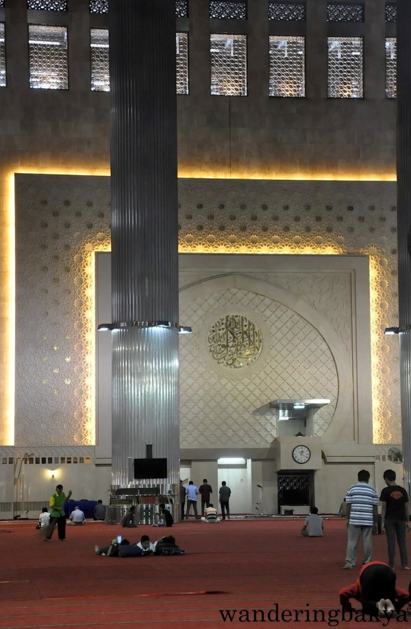 The two large metalwork that hang on either side of Surah Thaha 14th verse are  Arabic calligraphy spelling the name of Muhammad on the left side and Allah on the right side.