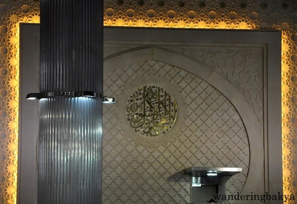 On the main wall hangs the  metalwork that has Arabic calligraphy Surah Thaha 14th verse.