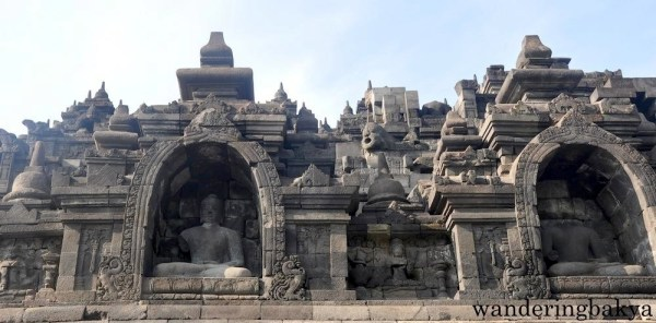 The view of Buddha statues and other details of Borobudur temple as seen from outside the temple