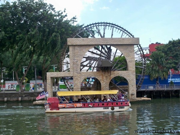 A boat full of people traversed the Melaka River for a faster way to tour the area.