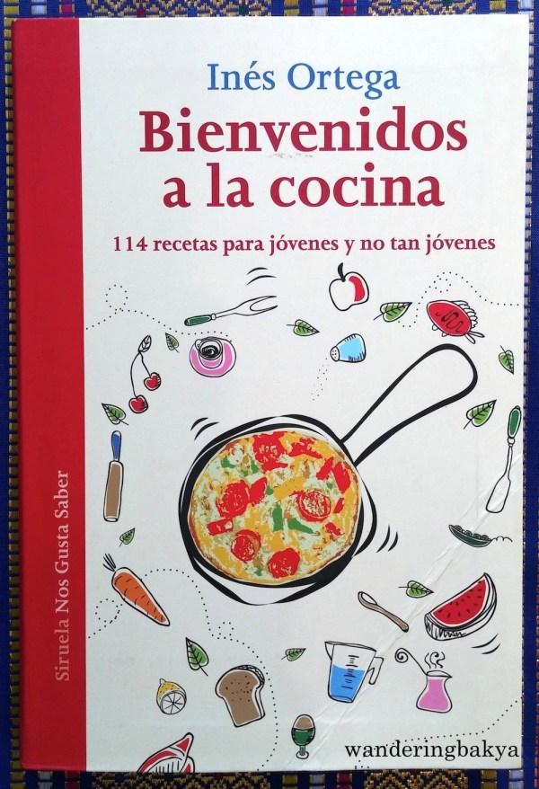 Bienvenidos a la Cocina by Inés Ortega. This one is very good. It has appetizingly wonderful photos and some recipes are not complicated. It has recipes for macarrones a la Popeye, carlota de chocolate, yemas, crepes and tostadas de jamón y piña.