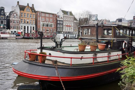 Houseboat parked across tall buildings on canal