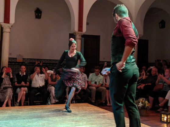 A male and a female flamenco dancer facing each other. His hand is extended and her hands are swinging her skirt to one side with one leg forward.