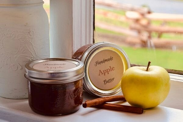 2 small jars of canned apple butter sitting on window sill with an apple and two cinnamon sticks