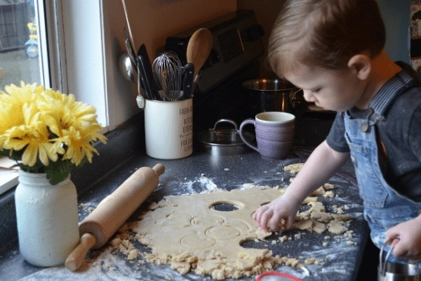 boy cutting scone dough and biscuit cutter