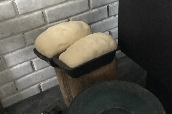 two loaves of bread rising by the wood stove