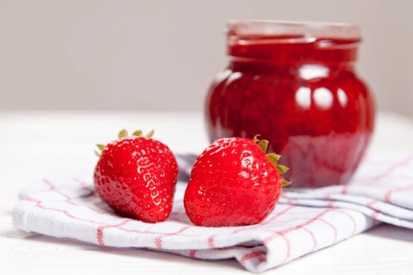 jar of strawberry jam and two strawberries on tea towel
