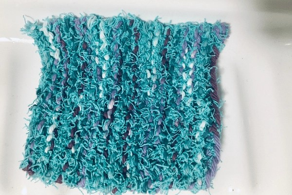 Dishcloth Scrubby sitting on sink shelf in purple and turquoise blue, Wandering Hoof Ranch brand colours