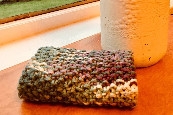 folded Knitted dishcloth sitting on table next to vase by window. Purple and blues and whites in this pretty seed stitch pattern and texture