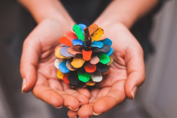 person holding a painted pine cone in the palm of their hands, each piece is painted a different colour of the rainbow