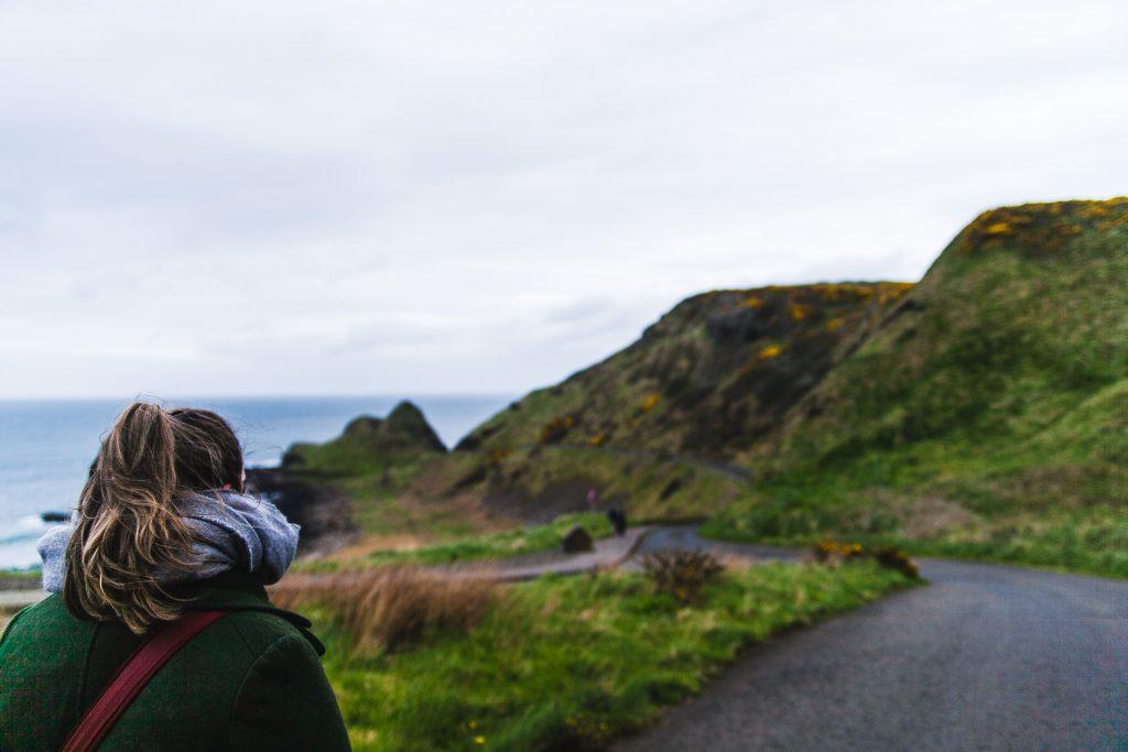 girl looking down road ireland coast