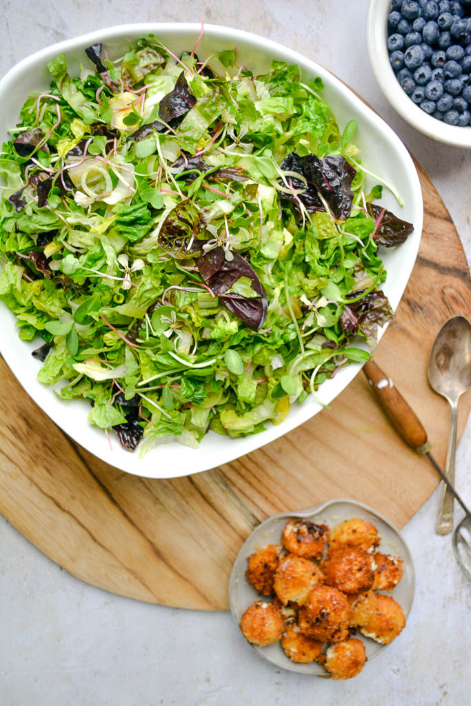 Bowl of spring salad with lettuce, microgreens, and herbs