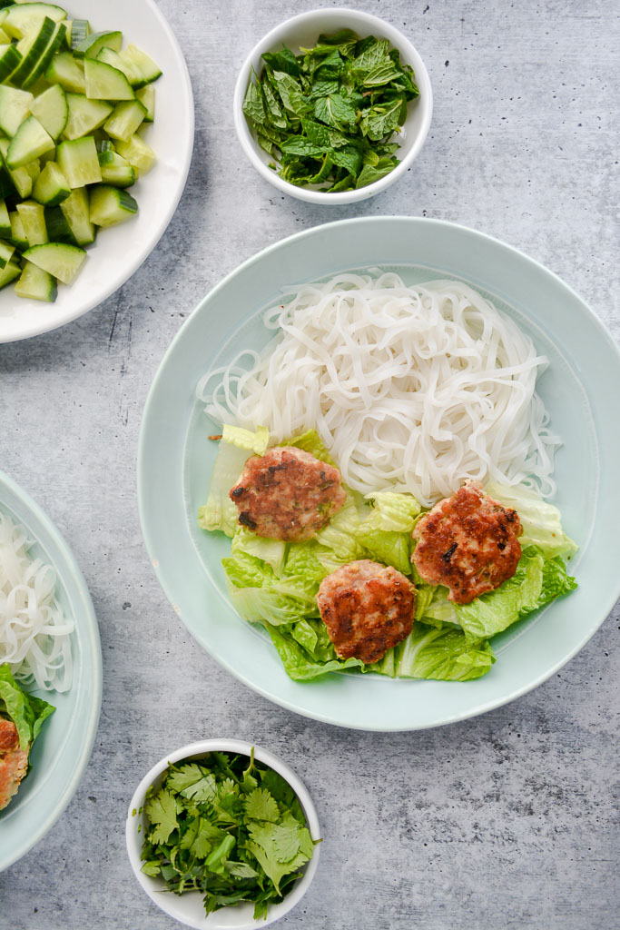 Bowl of cold rice noodles, romaine lettuce, and pork meatballs