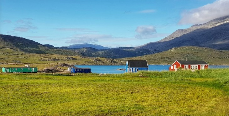 sparse but colorful houses by the water near Igaliku greenland.