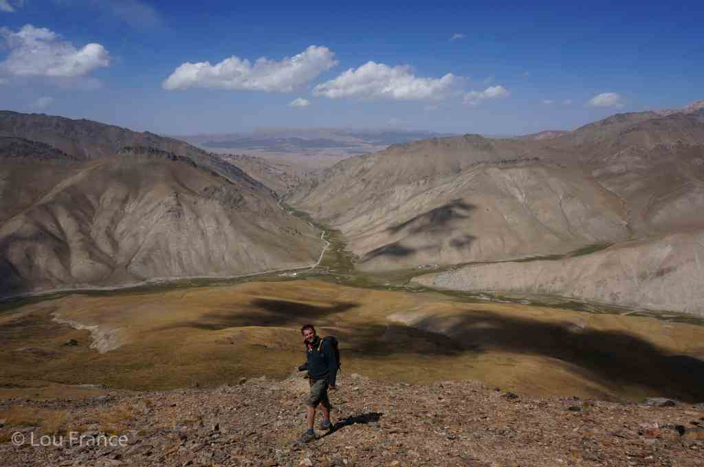 A man hiking amongst arid mountains. Hiking is on of the best things to do on a visit to Kyrgyzstan