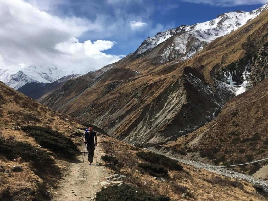 Nick hiking the Annapurna circuit trail. Trekking poles are an inclusion on this Annapurna circuit packing list