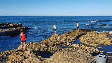 Fishing off the rocks at Otarawairere Beach