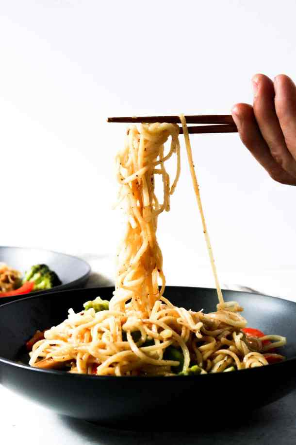 lo mein noodles being picked up with chop sticks