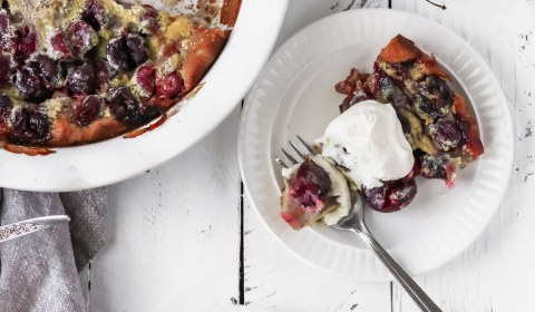 two slices of cherry clafoutis on plates with homemade whipped cream