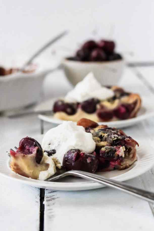 two pieces of cherry clafoutis on a plate with homemade whipped cream