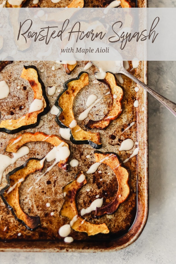 roasted acorn squash on a baking sheet, drizzled with maple aioli