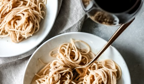 two bowls of cacio e pepe with a glass of red wine